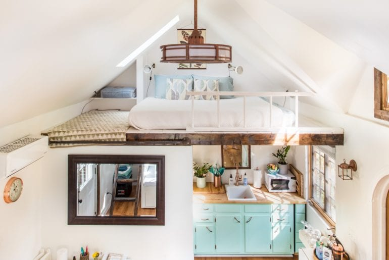 The space in this tiny home is utilized creatively with a loft style bedroom.