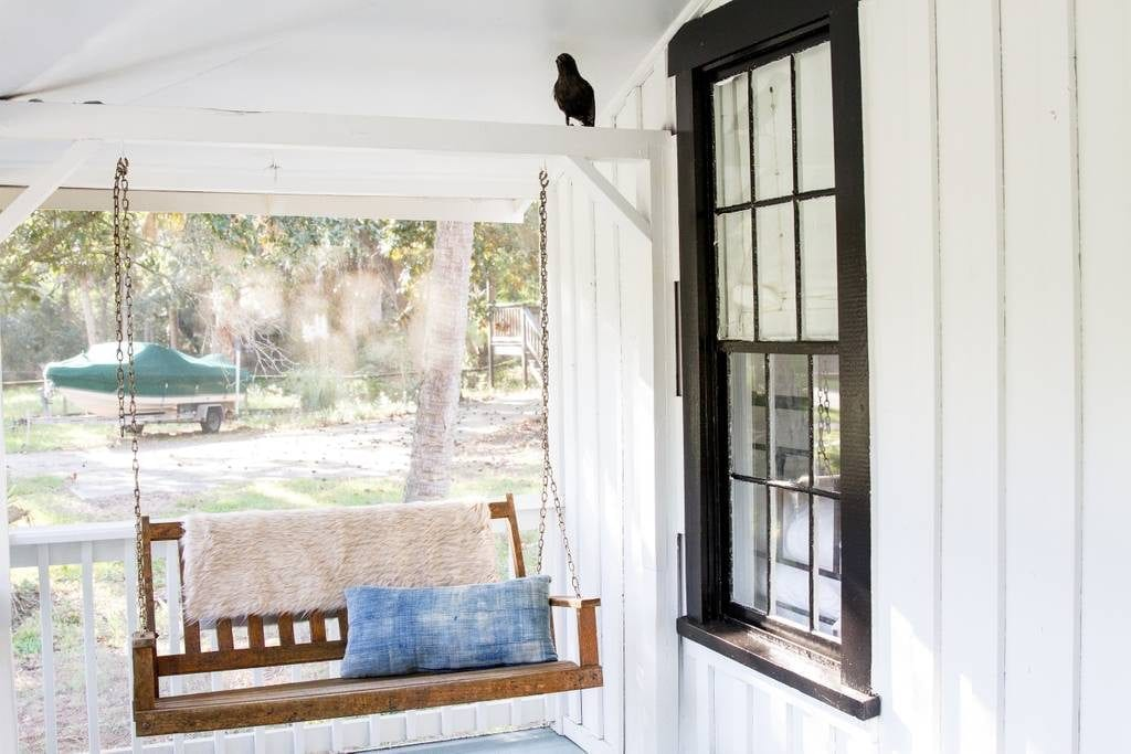 Serene swing hangs from the porch of this vintage Folly Beach cottage