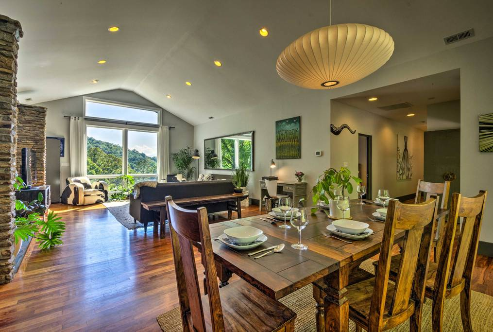 Open floor plan living and dining room, featuring rugged dining table, stacked stone wall, and cow skin arm chair
