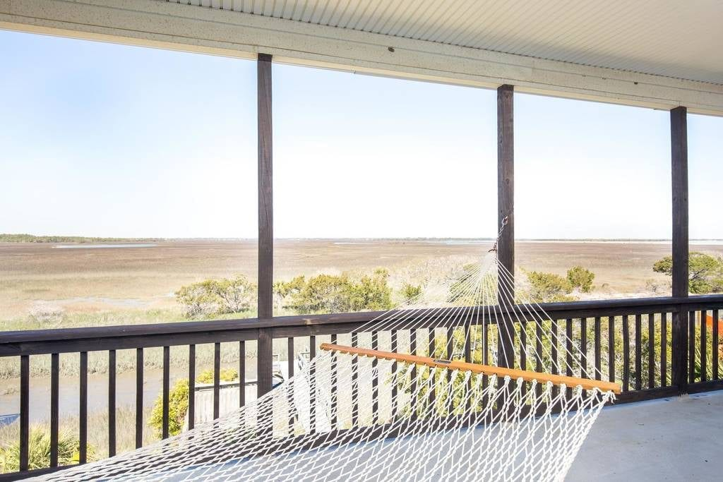 Hammock swings in this screened-in porch overlooking the marsh at Charleston Airbnbs near beaches