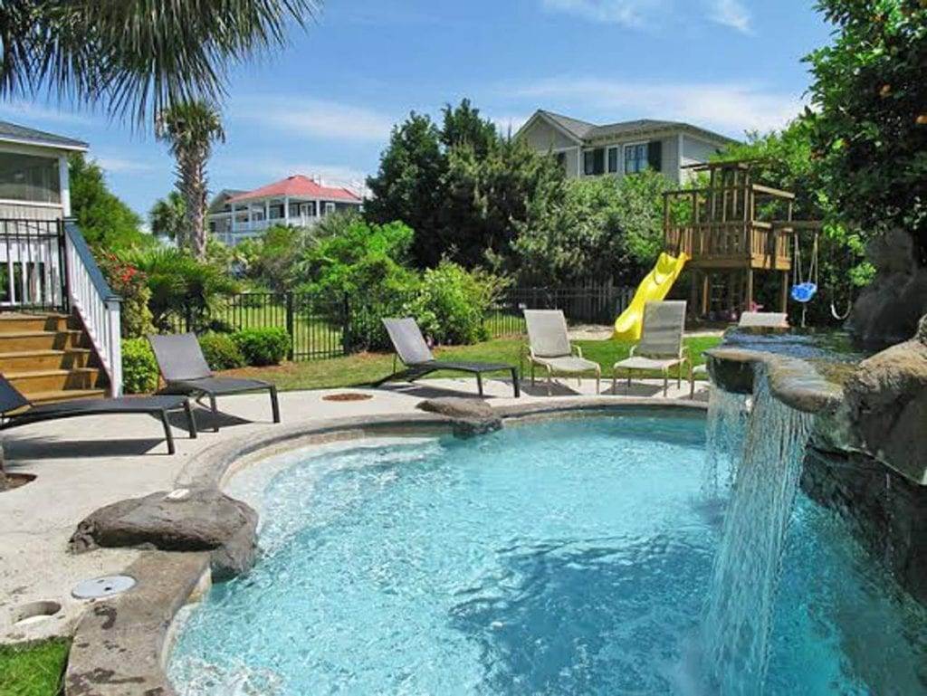 Backyard paradise for families with this private playground and in-ground pool with a waterfall feature