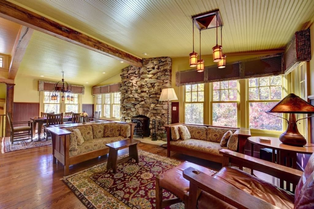 Open floor plan of a living/dining room featuring a stacked stone hearth
