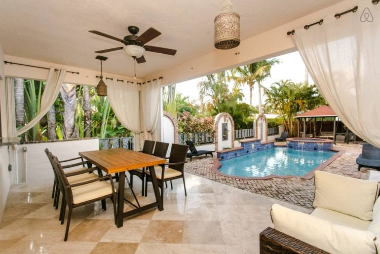 a dining area by a blue pool in West Palm Beach
