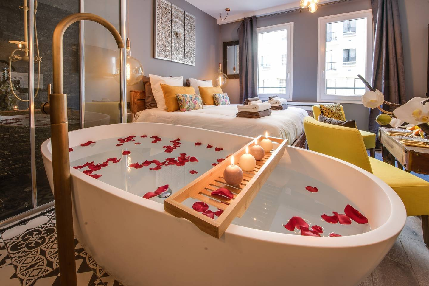 a stand alone bath tub with rose petals