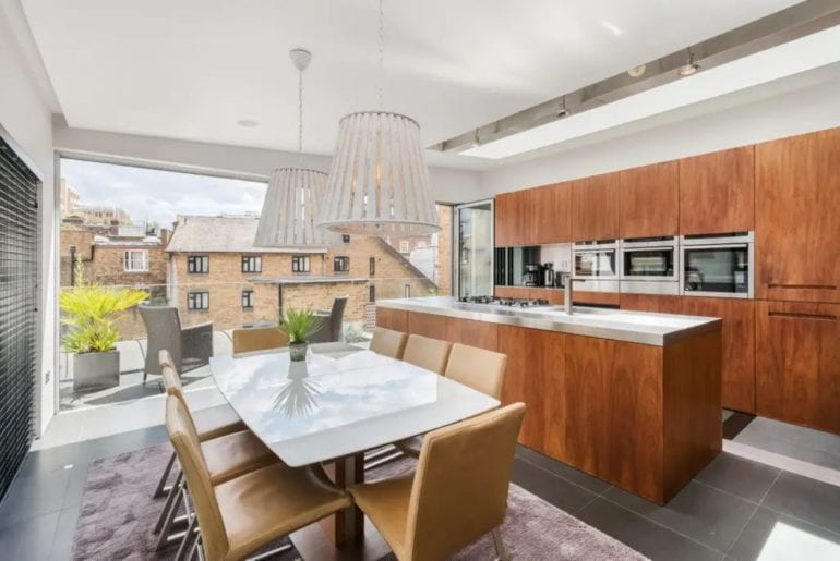 a stylish dining room with giant glass windows overlooking London