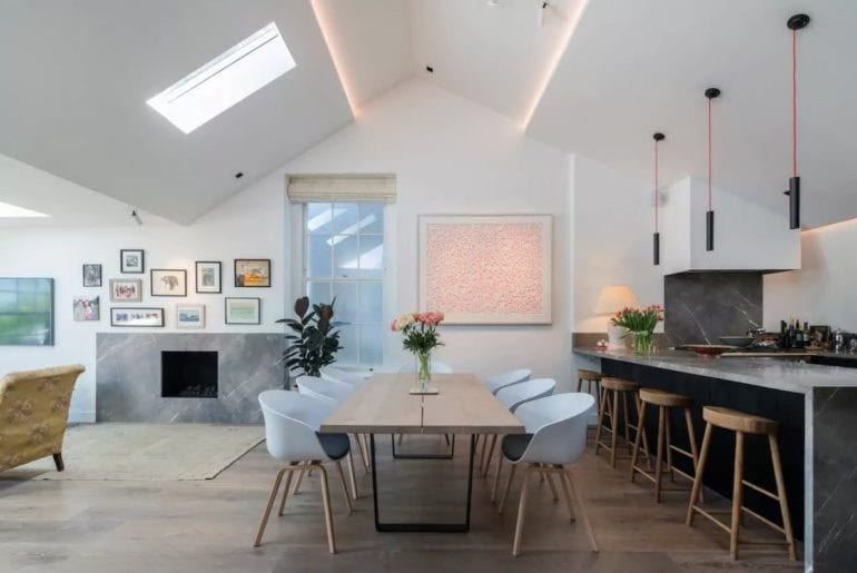 stylish London Airbnb dining room with white chairs and art on the walls