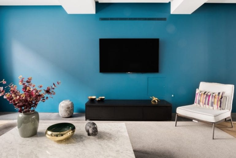 blue wall with mid century chair and elegant marble coffee table in the foreground