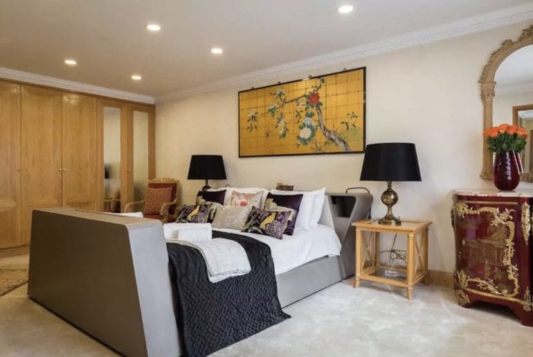 grey modernist bed with gold artwork above it