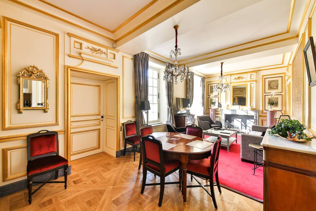 a gorgeous living area with gold paneling in Paris