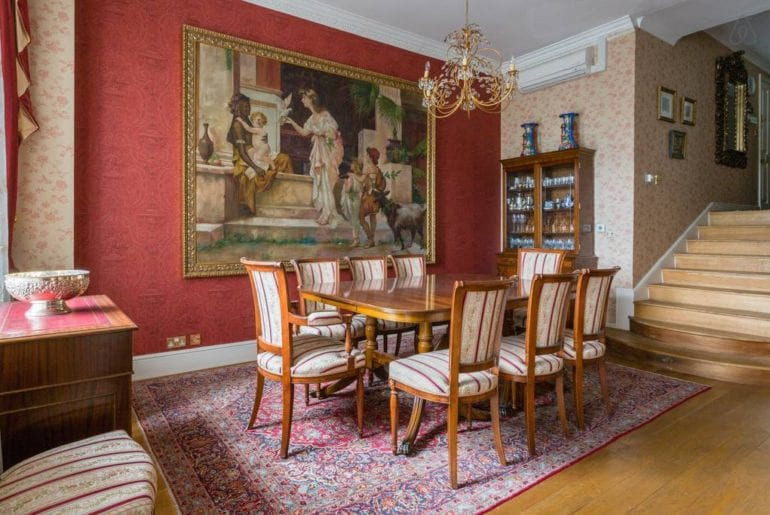 A wooden dining table with a painting behind it and a chandelier over it