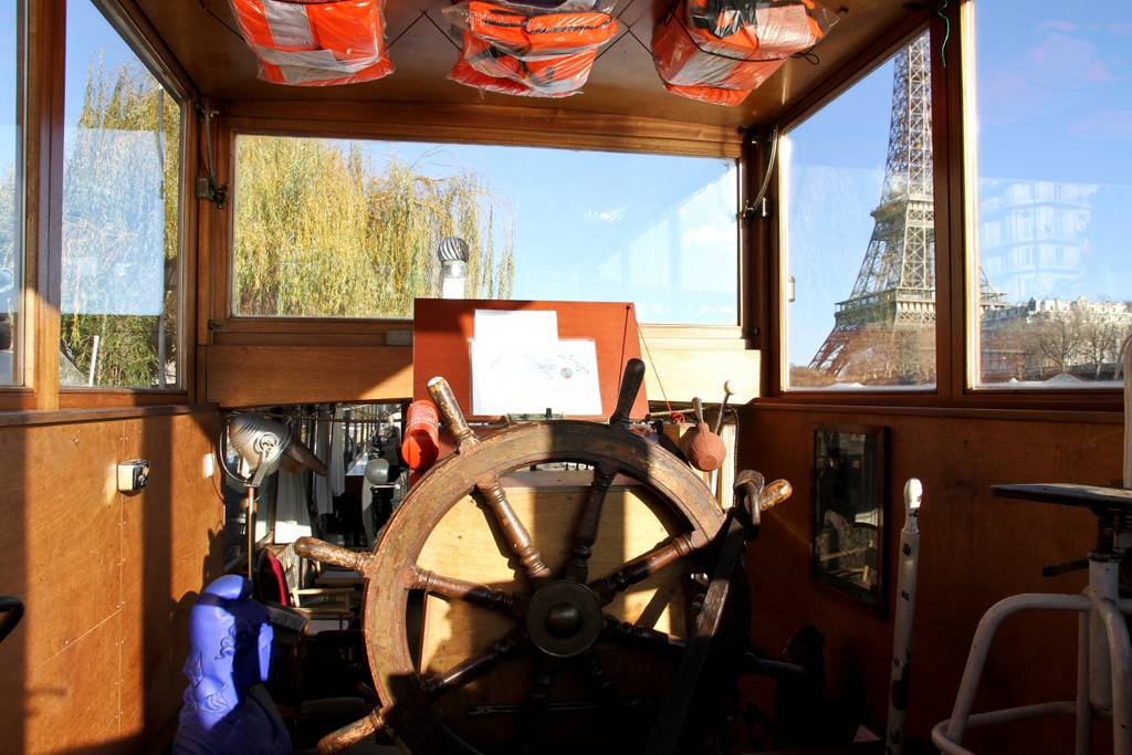 incredible houseboat docked in front of eiffel tower