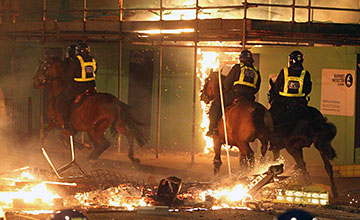 Hot Pursuit: Mounted police officers chase rioters amid the flames in Totterham, where the riots began. -Click image to expand.