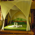 Bed with mosquito nets at the Swasti Eco Cottages