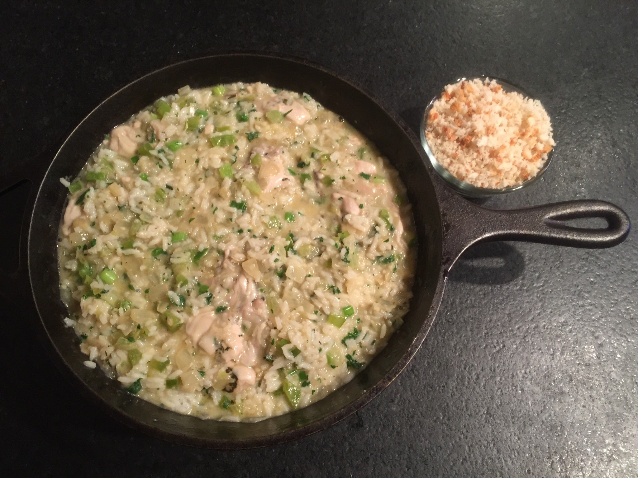 Deep skillet filled with oyster, rice and trinity mixture, ready for breadcrumb topping.