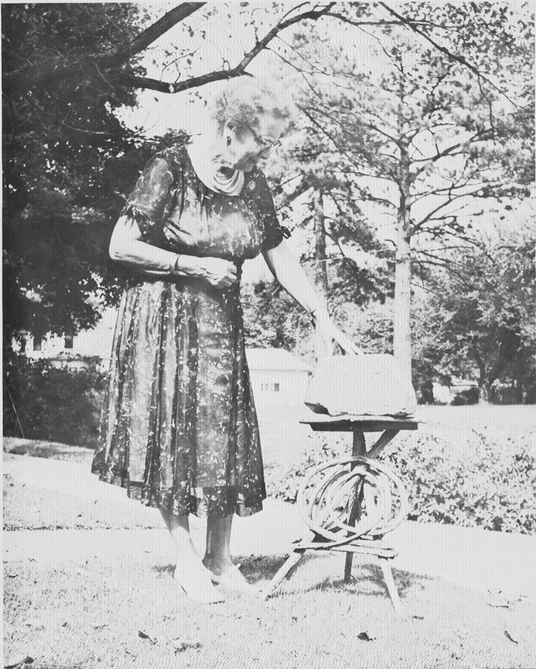 Elsie Gault is shown with a stone with the date 1867 carved into it. The stone was originally part of the springhouse near the cabin and is currently displayed in the cabin.