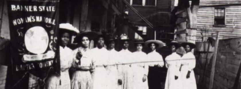 Several African American women stand with a banner promoting their women's suffrage organization.