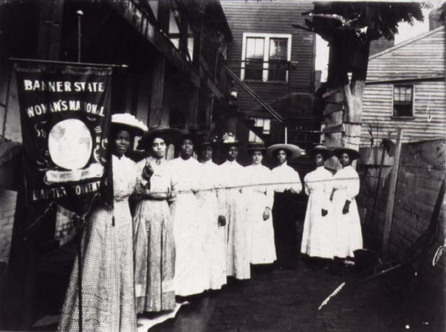 Several African American Women lobbying for the right to vote stand in a line.