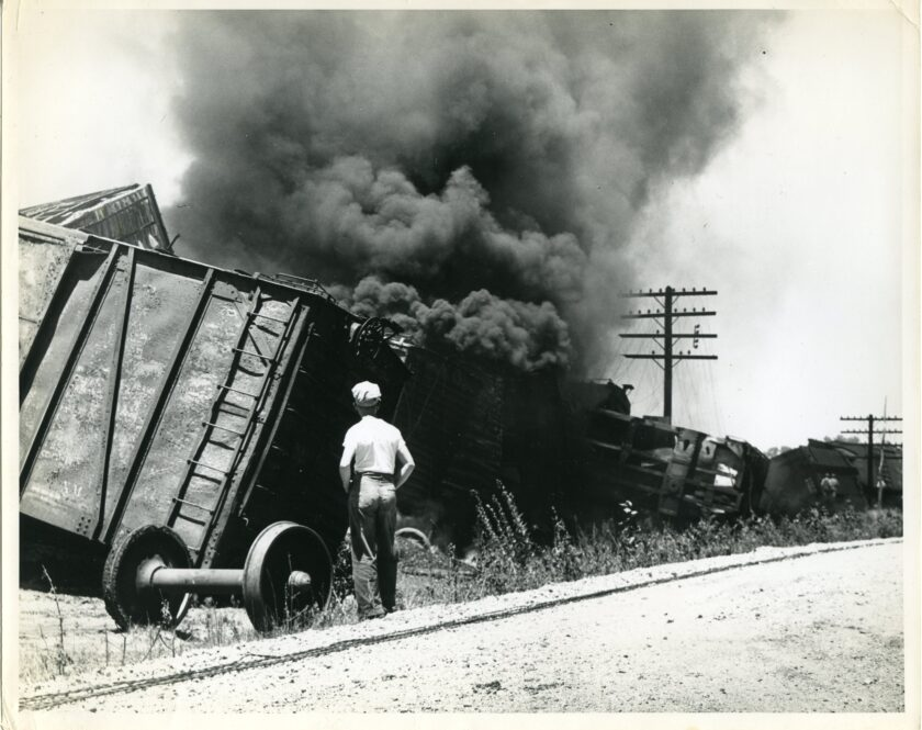 Un unidentified male stands near a set of wheels detached from a freight car. The railroad cars are derailed and on fire. Large clouds of black smoke fill the air.