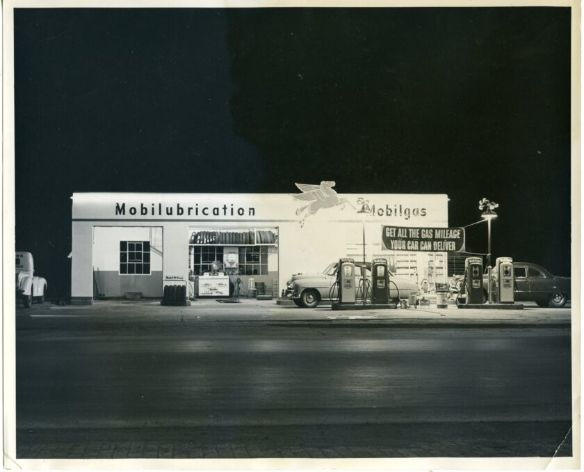 In this black-and-white image shot at night, the Mobilubrication station, a brightly lit white building, stands along an empty street.