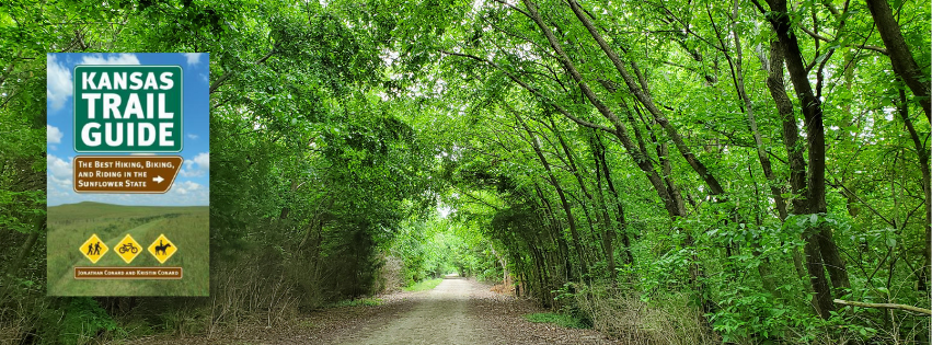 Green-leafed trees arch over a gravel trail. A book cover for Kansas Trail Guide is highlighted on the left.