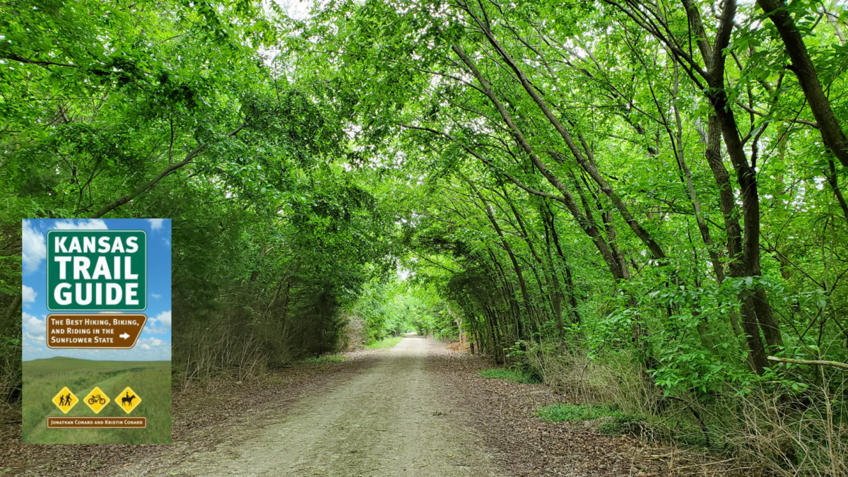 Green-leafed trees arch over a gravel trail. The cover of the book Kansas Trail Guide is highlighted in the lower left corner.
