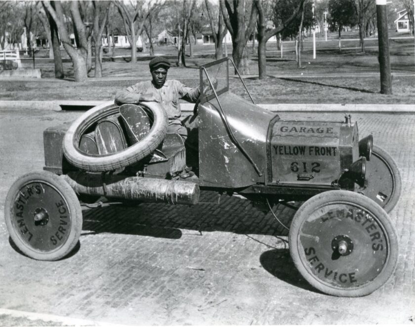 """An African American man sits behind the wheel of a 1920s race car, which is parked in front of City Park. Trees and a pedestrian bridge are visible in the background. The man rests his arm on a tire. Printed on the car are """"Lemaster's Garage Yellow Front"""" and """"Lemaster's service."""""""