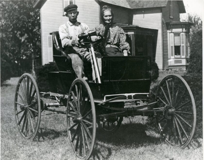 And elderly man and woman sit in a very early automobile, which is parked in front of a house.