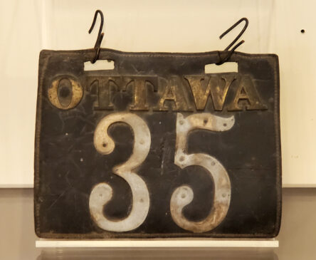 """A black leather license plate with the name """"Ottawa"""" and number 35 in metal."""
