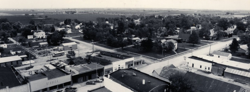 Aerial view of a street lined with businesses and cars.