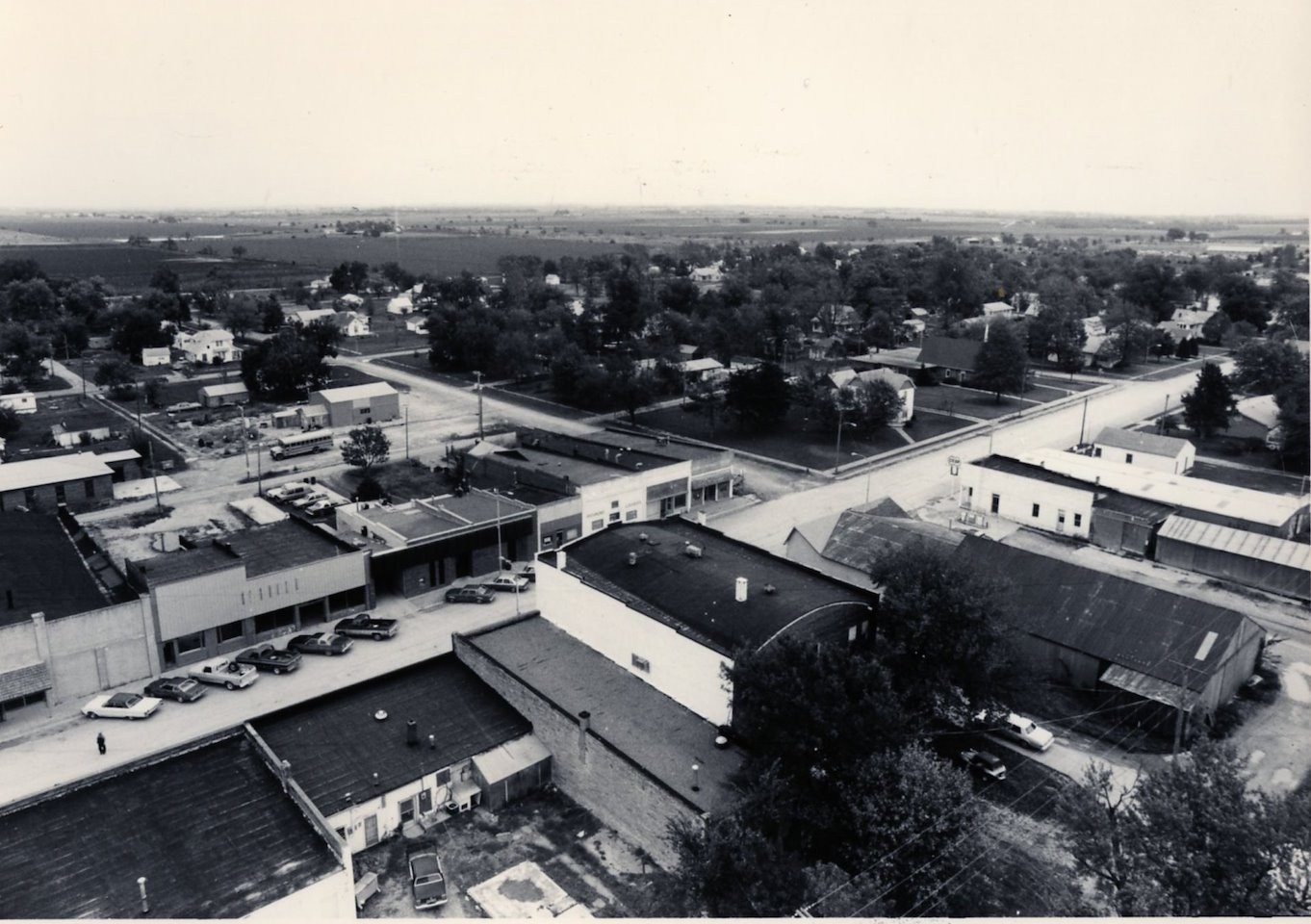 An aerial view of a street lined with businesses and cars.
