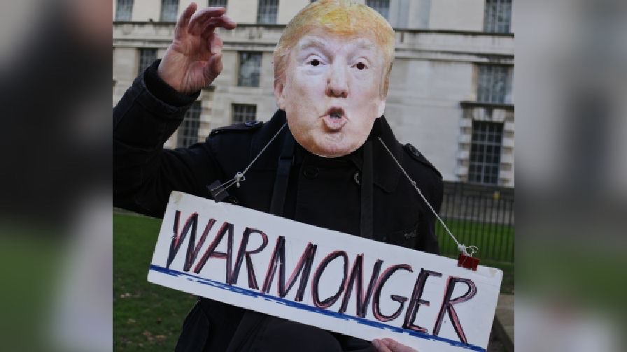 Protester dressed like Trump with sign saying warmonger hanging from their neck