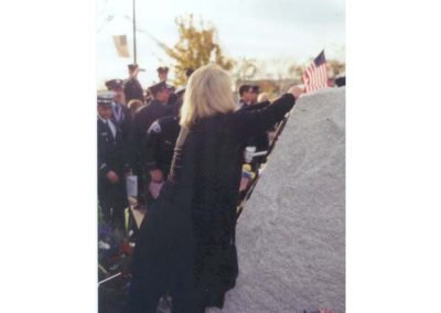 Linda Zoerb placing flag on memorial