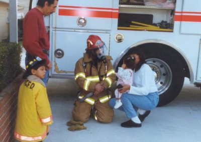 Ron showing fire equipment to children