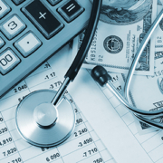 Calculator, hundred dollar bills and stethoscope on top of financial records.