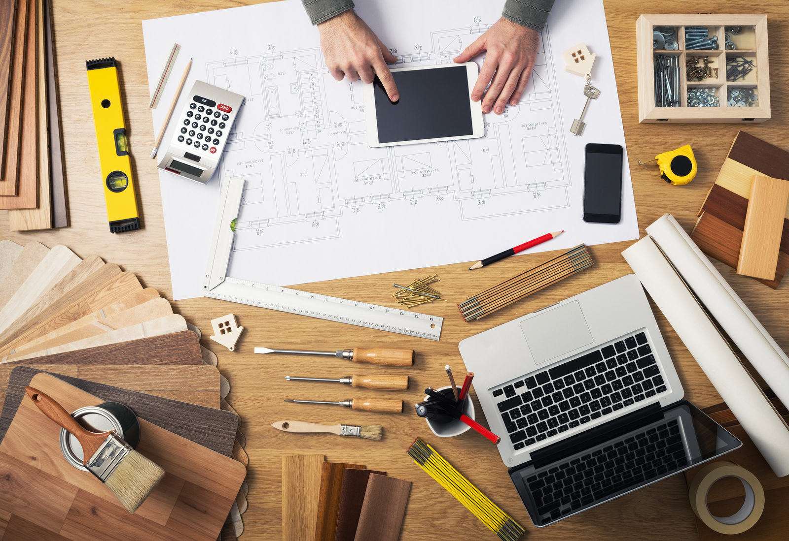 Construction engineer and architect's desk with house projects laptop tools and wood swatches top view male hands using a digital tablet