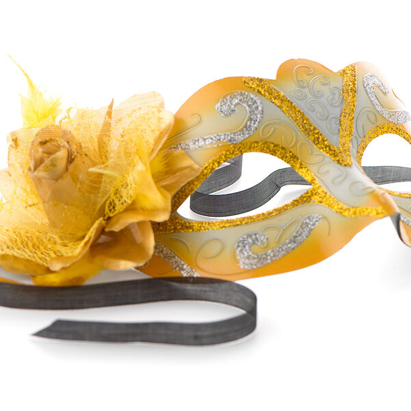 Yellow venetian mask for a party on a white background ** Note: Shallow depth of field