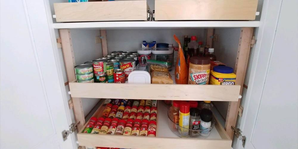pullout shelving in kitchen cabinet stocked with spices and food items