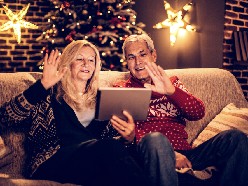 Lakeside-Living_Manitowish-Waters-WI_How-to-Show-Your-Loved-Ones-You-Care-This-Holiday-Season_Couple-on-iPad-Chatting-with-Family-at-Christmas-Time