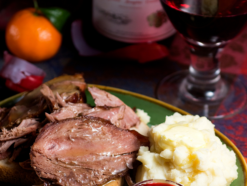 Lakeside-Living_Manitowish-Waters-WI_How-to-Show-Your-Loved-Ones-You-Care-This-Holiday-Season_Holiday-Meal-of-Meat-and-Mashed-Potatoes-with-Wine-Nearby
