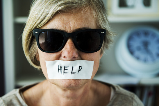 Senior woman with sunglasses and tape on her mouth, victim of domestic violence