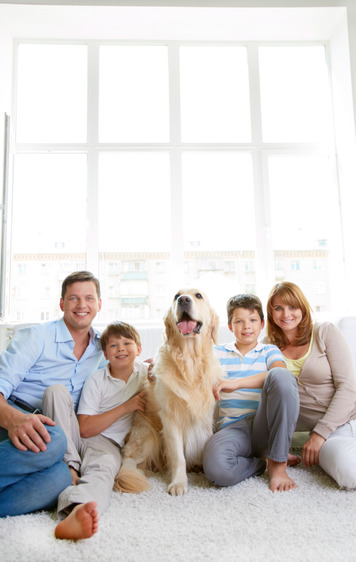 Cheerful family with their pet sitting on the floor at home