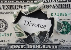 Hole ripped in a dollar bill with Divorce text