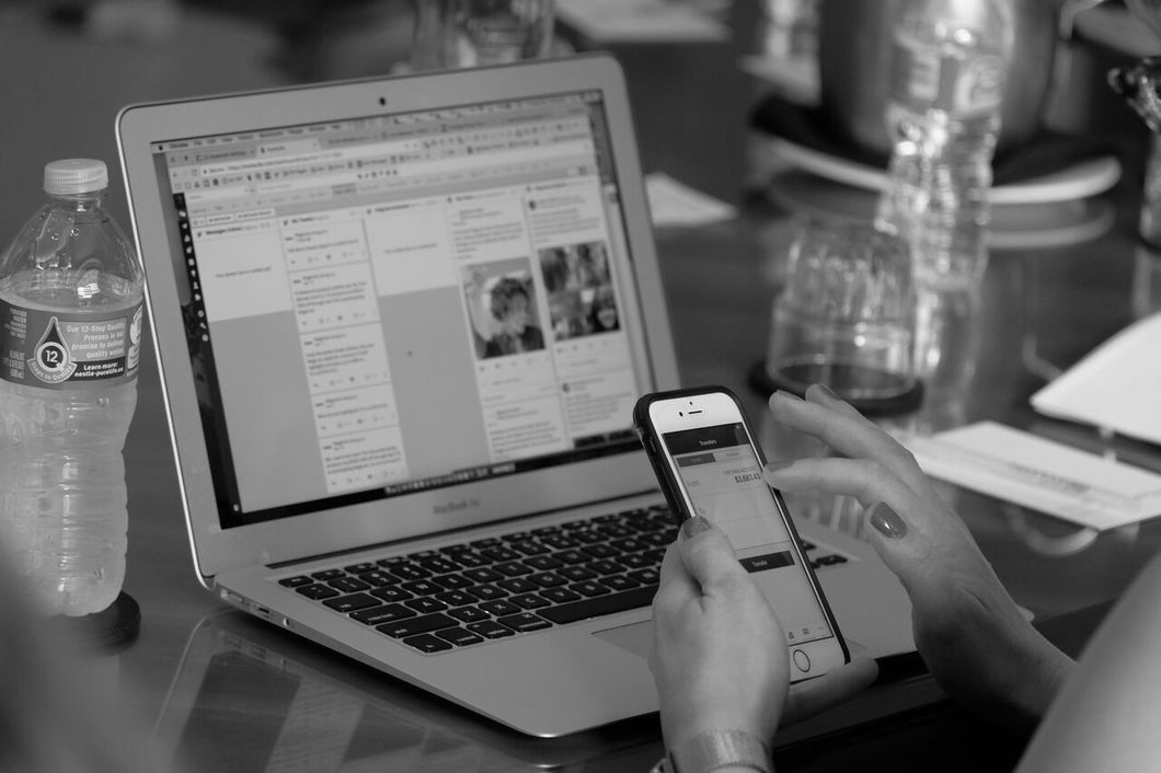 PR professional using laptop and phone to check social media
