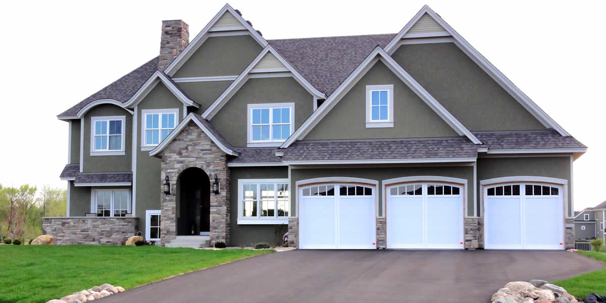 Home with siding, roofing, windows, soffit, facia, trim, and stone work