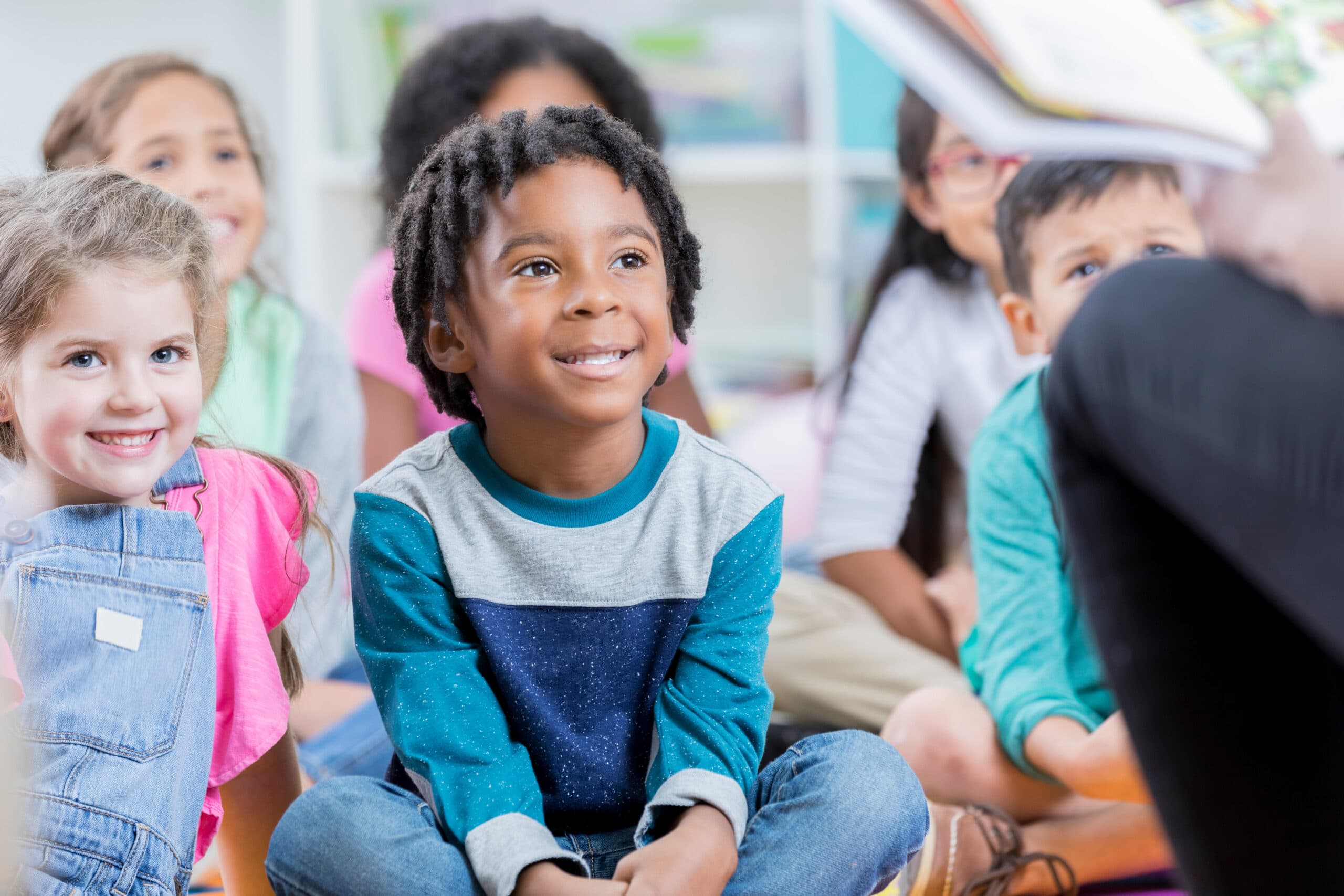 An attentive little elementary age boy sits with his friends on the floor during an after school program.  He looks up as he listens to a sitting unrecognizable child care worker read a book.