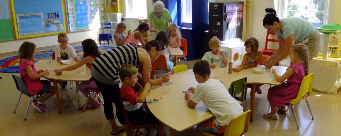 teachers assist children in Sunday school classroom
