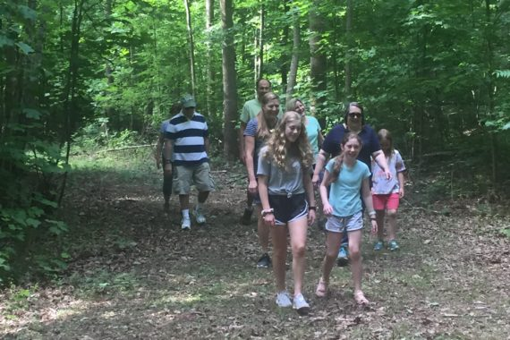 people walk on wooded trail