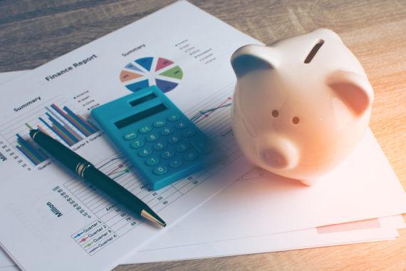 financial charts, calculator, and piggy bank