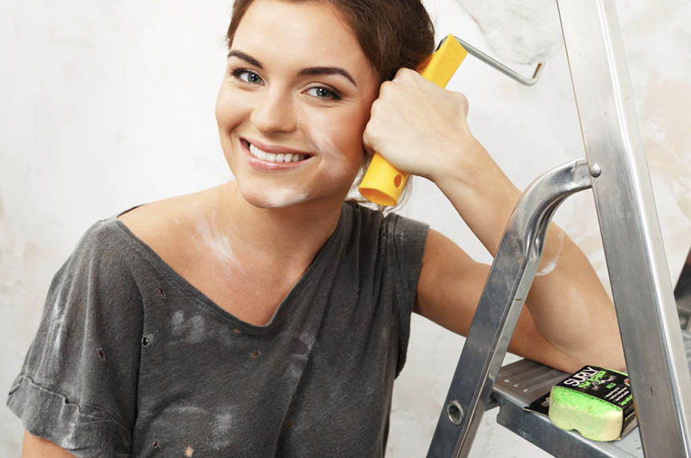 woman holding paint brush with mild bar of SURLY Soap