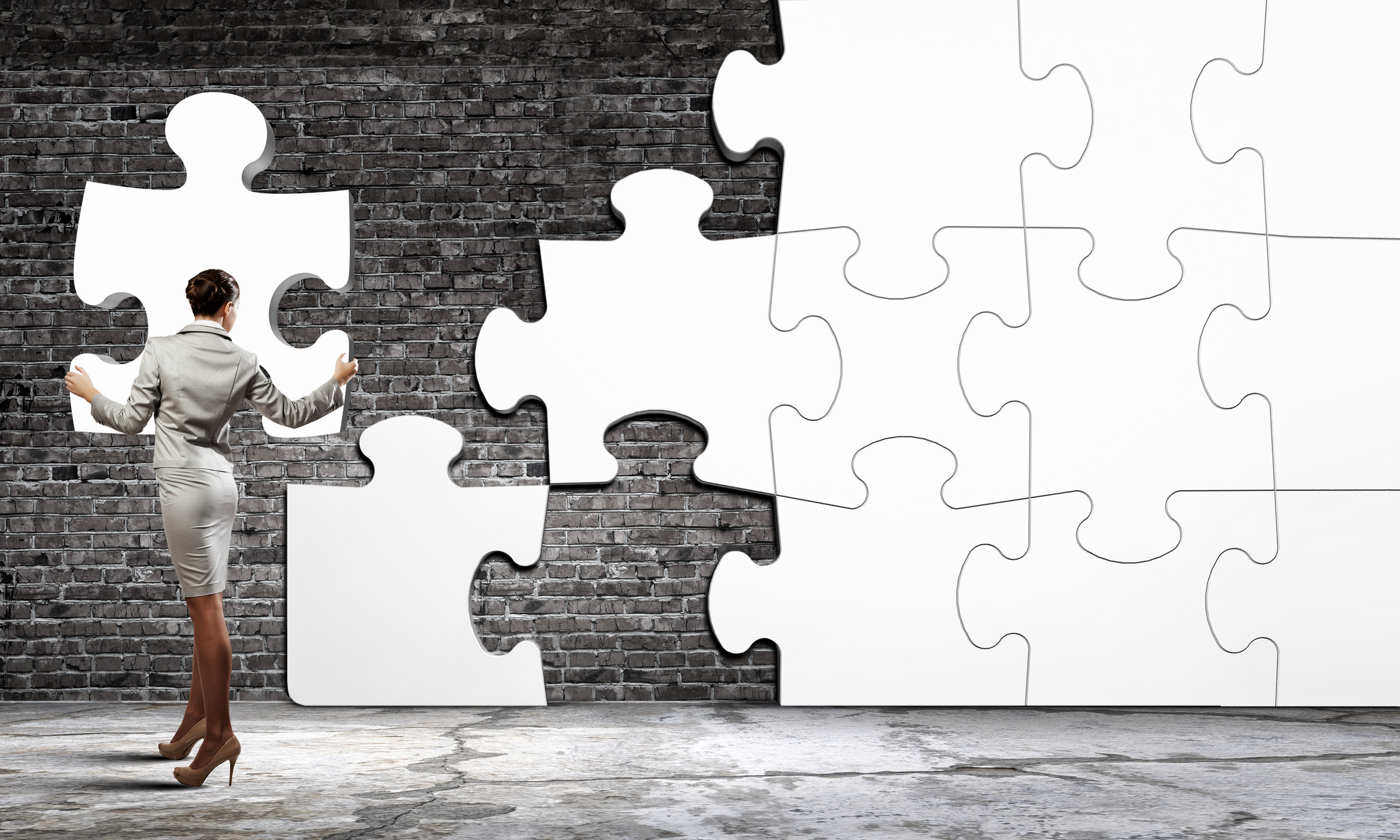 businesswoman connecting elements of white puzzle